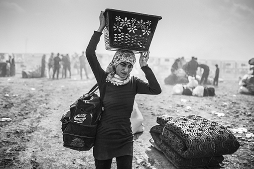A Syrian Kurdish woman has just crossed the border separating Syria from Turkey. She arrives in the city of Suruc, located in the province of Sanliurfa, with what she could carry in the rush of departure. Suruc - Turkey, September 2014. In September 2014, ISIS started to attack Kobani and besieged the city on October 2014. In the town, thousands of people tried to survive. In order to escape the clashes, even children and elderly people didn't hesitate to cross over the mine fields that separate Kobani from the turkish border. According to UNHCR, 170,000 inhabitants of Kobani took refuge in the camps in Turkey.
