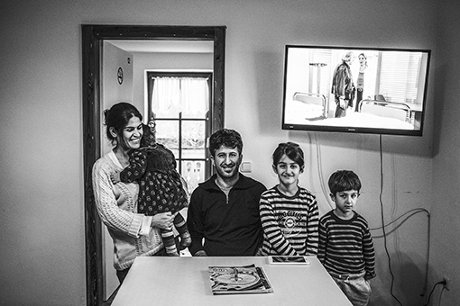 Iraqi Kurdish refugee family (left to right) Dunya Abdullah (31) Hemn Abdullah (32) poses with daughters Reyan and Honya and son Dlovan in a common room of a refugee home. Rettiszell - Germany, november 2015. They got a room in this common house from German State in Rettiszell town near Straubing and living with 18 other refugees. Before, they were living with three hundred refugees in a gymnasium which has been prepared for the first period of the arriving refugees. According to German authorities (7th of december 2015), nearly one million asylum seekers have registered in Germany in 2015.