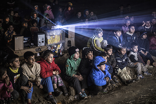 Refugee children watching movie in a cinema under the open sky, made only for them at the refugee camp at the border. Eidomeni is now worldwide known for a sad reason. 12.000 refugees among them children, old women and men are stuck on the borders between Greece and Macedonien.