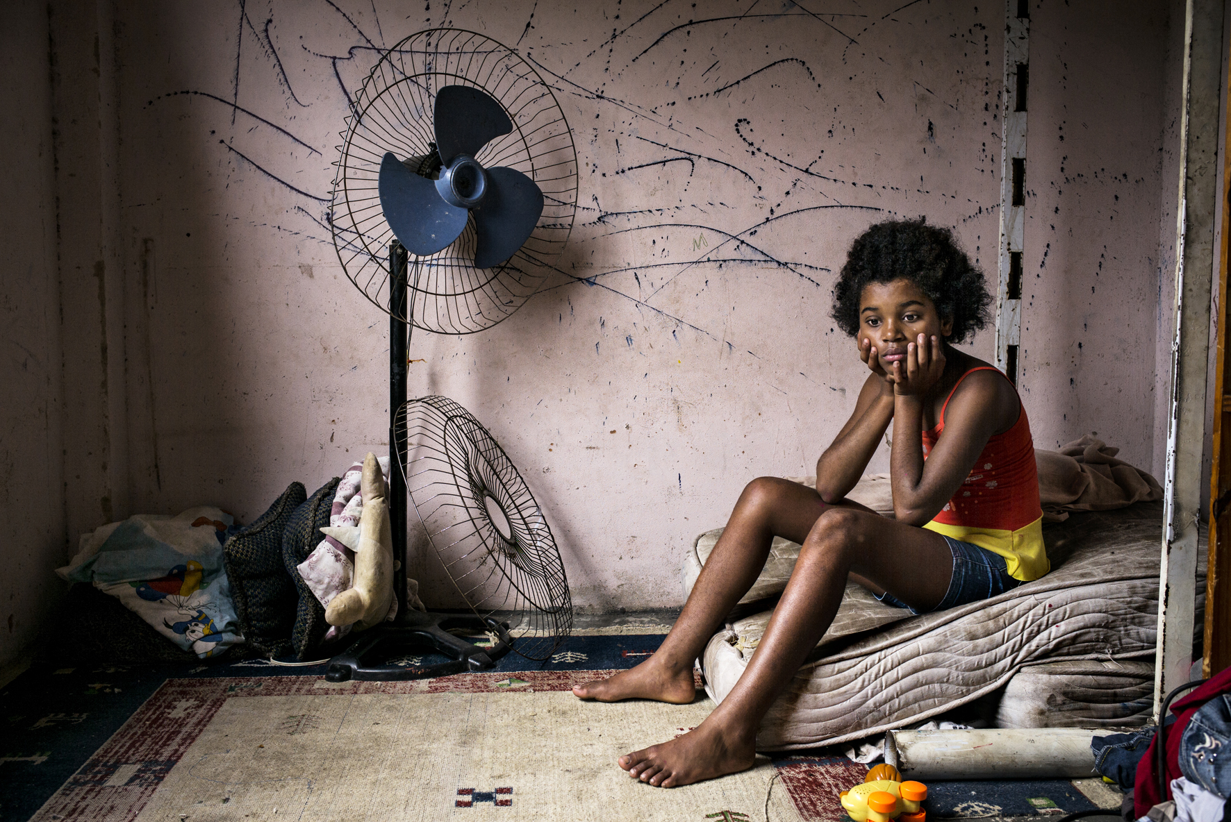 Maria Eduarda is sitting in her simple bedroom that she shares with 4 more siblings. She don't share only their rooms, they have also share the mattresses.