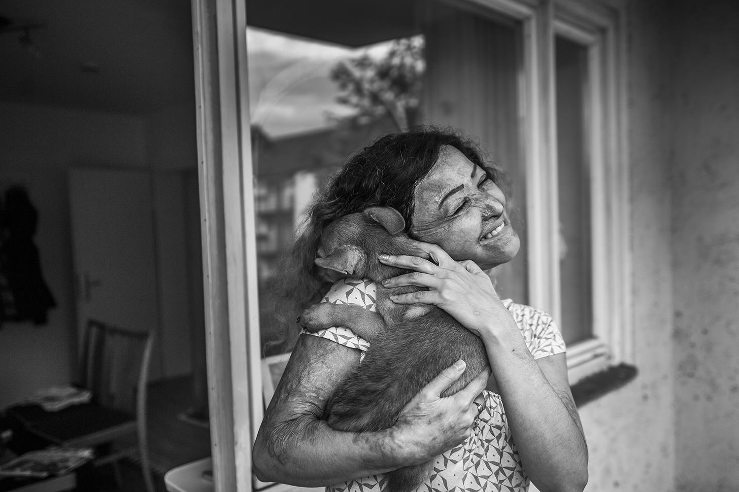 NavidBookani-012 Tahmineh Yusefie, victim of an acid attack, stands on her balcony, smiles and cuddles her dog. In the background we can look inside her living room in her flat in Hanover, Germany, the house opposite is mirrored in the window. July 22, 2016 Significance of the photo: Despite her pain and her past she still has joy, tenderness and hope. What cannot be seen in the picture, is that she abandoned the dog a few days later. So the picture became a symbol for the trauma that left her craving for closeness and at the same time made her so incapable of bonding. Circumstances: Tahmineh invited the photographer for dinner at her flat in Hanover, Germany. They sat talking, when she played with the puppy he took pictures.