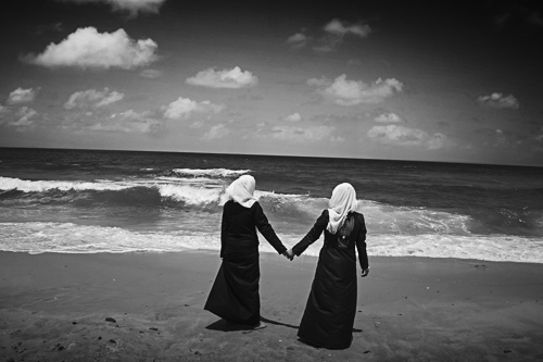 Gaza, Apr 2015: Two students are chilling on the seaside after their annual exam at school. Sea water is heavily polluted due to the high rate of raw sewage outlets discharging directly to the sea.